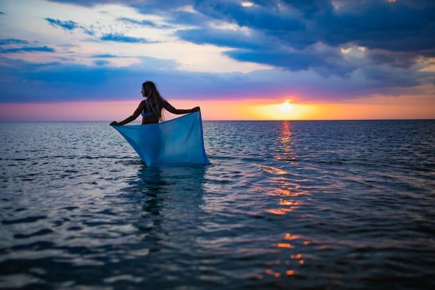 Una ragazza in costume da bagno blu e un pareo luminoso in posa sullo sfondo di un tramonto nell'estuario con acqua trasparente