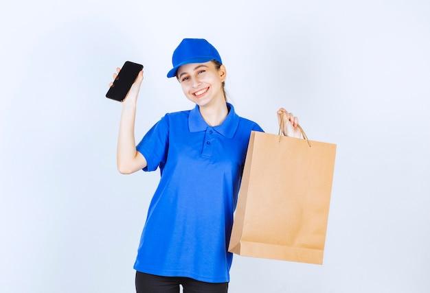 Ragazza in uniforme blu che tiene una borsa della spesa del cartone e uno smartphone nero.