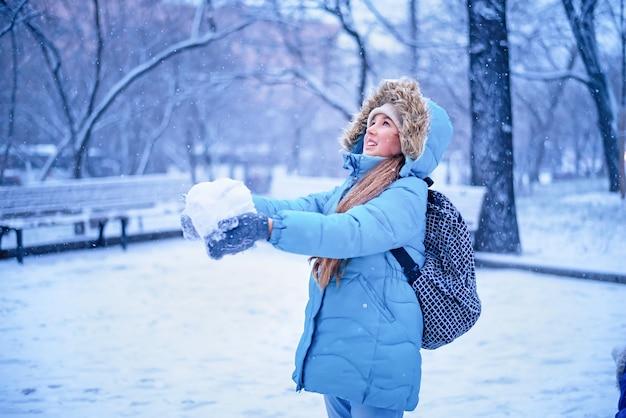 Ragazza in abiti invernali blu divertendosi con la neve. divertimento invernale.