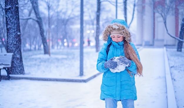 Una ragazza in abiti invernali blu gioca con la neve in un parco invernale.