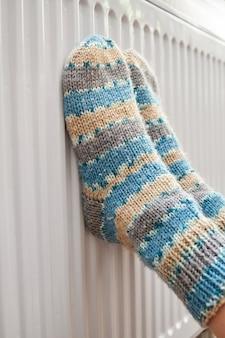 Una ragazza in calzini di lana blu scalda i piedi sul radiatore
