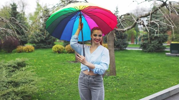 Ragazza in una camicia bluastra con trucco luminoso e lunghe trecce colorate. tenendo un ombrello nei colori dell'arcobaleno su un parco fiorito godendosi la prossima primavera