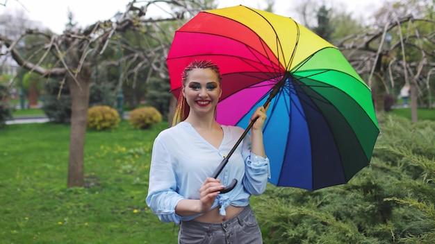 Ragazza in una camicia bluastra con trucco luminoso e lunghe trecce colorate. tenendo un ombrello con i colori dell'arcobaleno in un parco fiorito godendosi la prossima primavera