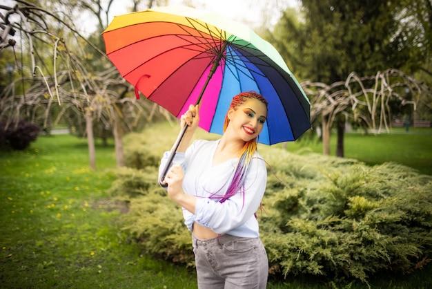 Ragazza in una camicia bluastra con trucco luminoso e lunghe trecce colorate. sorridente e con in mano un ombrello con i colori dell'arcobaleno sullo sfondo di un parco fiorito che si gode la primavera in arrivo.