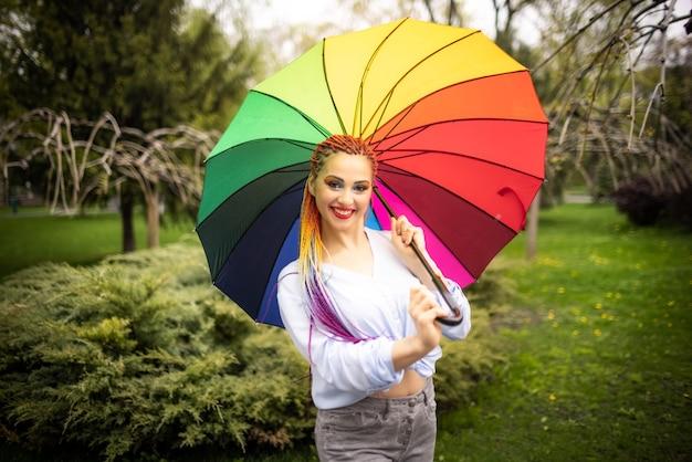 Ragazza in una camicia bluastra con trucco luminoso e lunghe trecce colorate. sorridere e tenere un ombrello