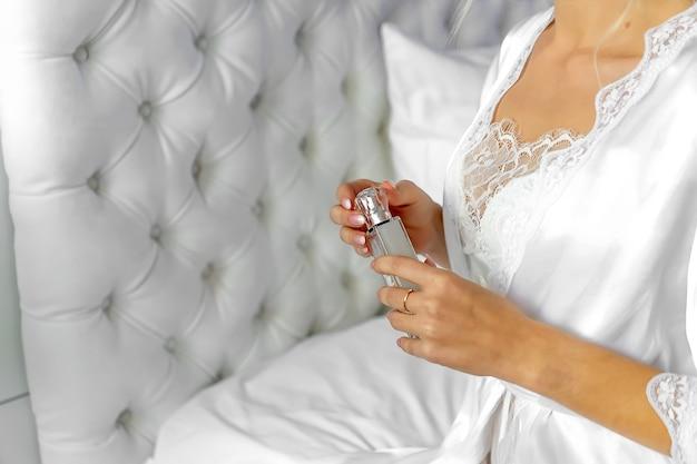 Una ragazza con un vestito da boudoir tiene in mano una bottiglia di acqua da toilette.