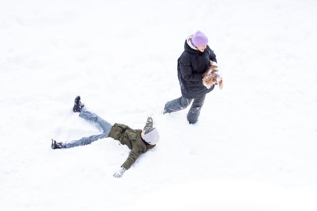 Ragazza e ragazzo si divertono all'aria aperta, il giorno nevica, sorella e fratello che ridono stelle filanti cane giocano a neve in abiti caldi invernali