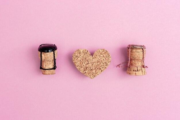 Personaggi di ragazza e ragazzo da tappi di champagne e muselets con cuore sul rosa