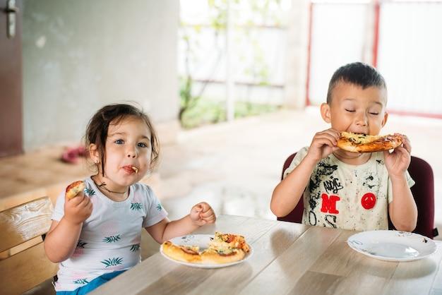 Una ragazza e un ragazzo, i bambini per strada mangiano una mini pizza molto appetitosa