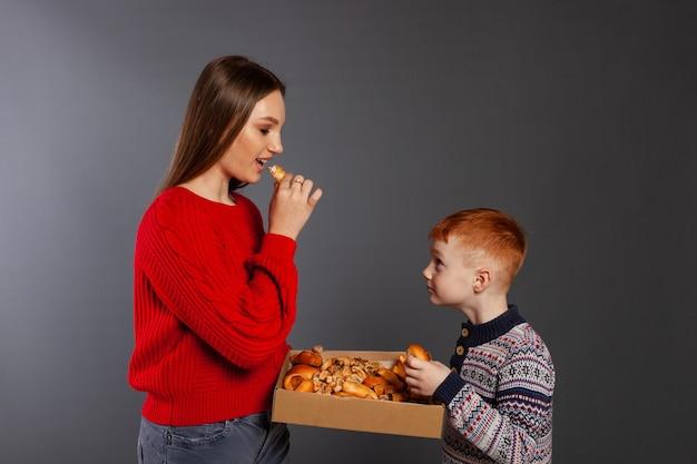 Una ragazza e un ragazzo mangiano torte di dolci da forno in uno studio fotografico su uno sfondo grigio