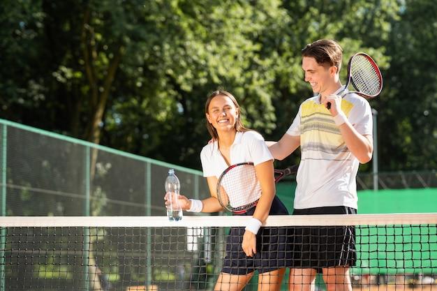 Ragazza e ragazzo con le racchette che giocano a tennis