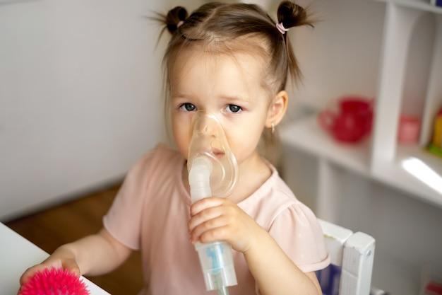Una ragazza respira in una maschera per inalazione