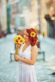 Sposa ragazza in abito da sposa con acconciatura elegante e con un bouquet da sposa