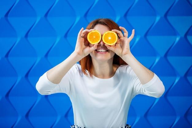 Ragazza su uno sfondo blu brillante in una camicetta bianca con arance in mano