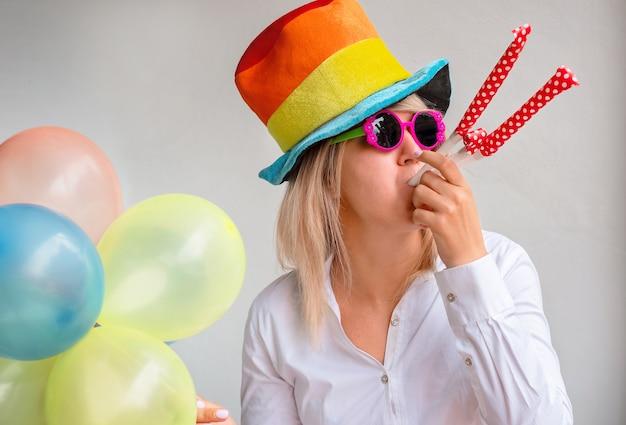 Ragazza in un cappello luminoso con occhiali da sole e palloncini sullo spazio
