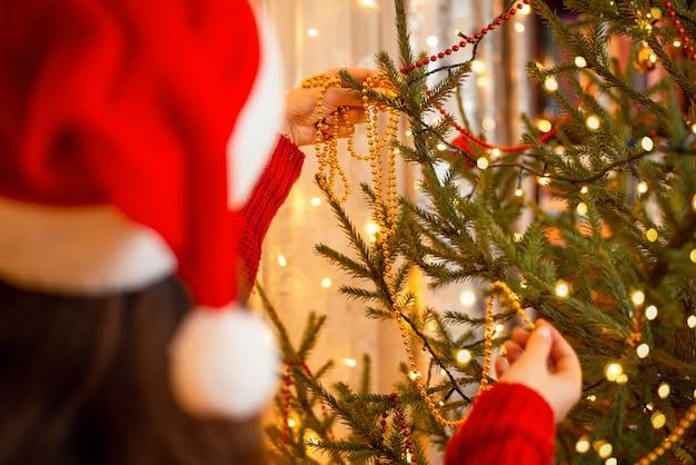 La ragazza in cappello di natale rosso e bianco brillante decora l'albero di abete con perline
