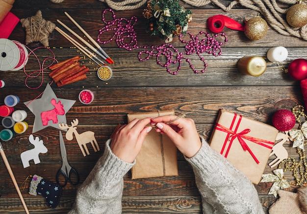 La ragazza in un maglione luminoso decora la scatola con i regali di natale