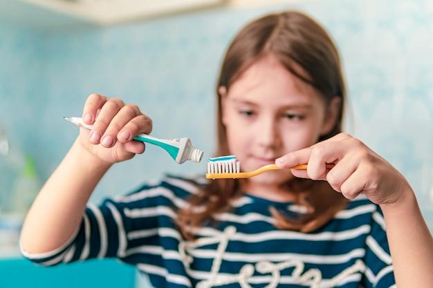 Ragazza che lava i denti in bagno. una bambina di aspetto caucasico che si lava i denti con uno spazzolino da denti, procedure igieniche al mattino.