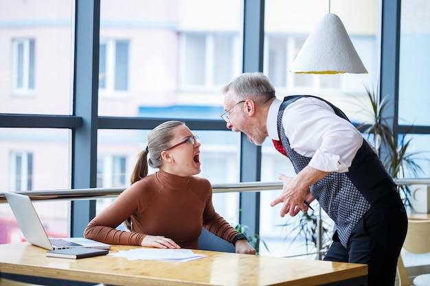 La signora d'affari della ragazza seduta a un tavolo di legno con un computer portatile e un mentore capo dell'insegnante di lavoro indica i suoi errori. urla e colpisce il tavolo con la mano