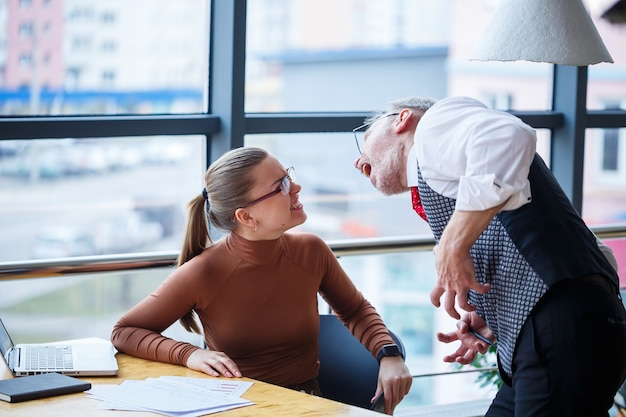La signora d'affari della ragazza seduta a un tavolo di legno con un computer portatile e un mentore capo dell'insegnante di lavoro indica i suoi errori. urla e colpisce il tavolo con la mano Foto Premium