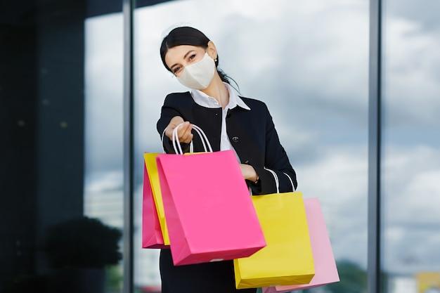 Una ragazza in giacca e cravatta e maschera con indosso borse luminose e tanti acquisti vicino al centro commerciale
