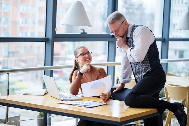 Donna d'affari ragazza seduta a un tavolo di legno con un laptop e discutendo un nuovo progetto con il suo insegnante capo mentore. l'uomo sta scherzando. nuovo concetto di sviluppo aziendale