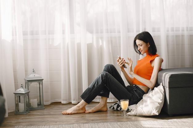 Ragazza vicino alla finestra sul pavimento utilizzando un telefono cellulare.