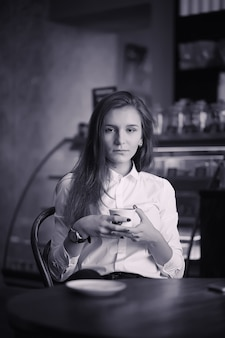 Una ragazza al bar sta bevendo caffè. una donna sta facendo colazione in un ristorante. caffè mattutino nella caffetteria per la ragazza.