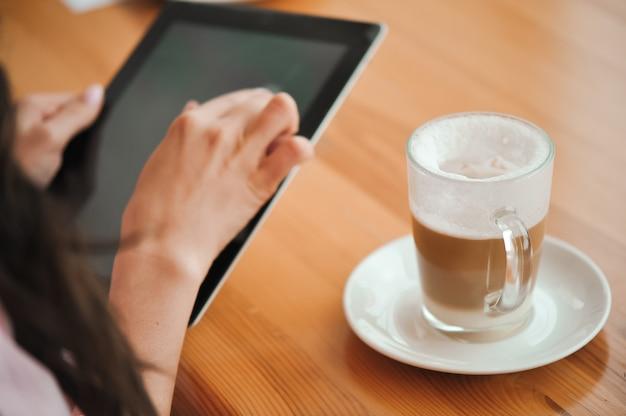 Ragazza in caffè utilizza un piccolo computer portatile.