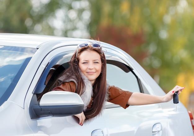 Ragazza in una macchina che tiene le chiavi in mano