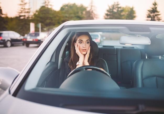 La ragazza in macchina è in un ingorgo.