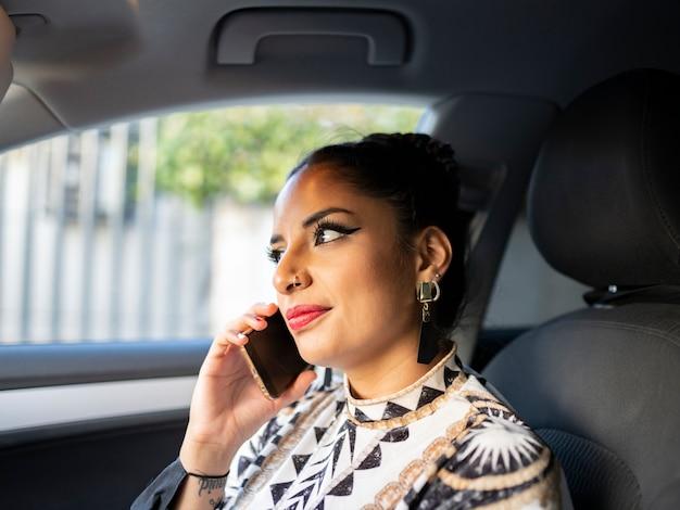 Ragazza in un seggiolino per auto parlando al telefono