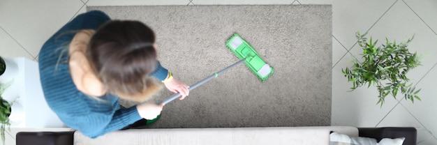 La ragazza pulisce con cura il pavimento nella vista superiore dell'appartamento