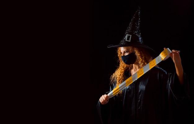 Una ragazza in un costume di carnevale e una maschera medica in attesa di uno spazio di copia di sfondo nero con nastro di avvertenza