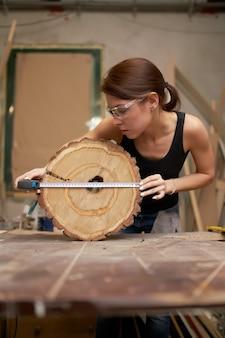 Carpentiere ragazza con metro a nastro e sega albero tagliato nelle sue mani in officina