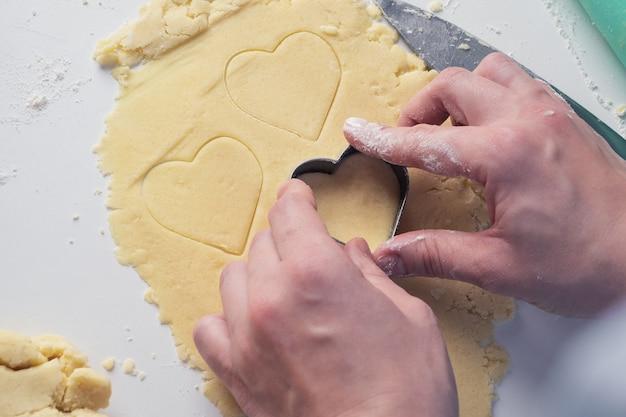 La ragazza scolpisce i biscotti a forma di cuore in cucina, a casa, primo piano. dolci fatti a mano con amore per san valentino, festa della mamma o festa del papà. sfondo culinario. cibo per le vacanze.