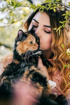 Ragazza e gatto. concetto di clima caldo primaverile o estivo. sfondo bokeh