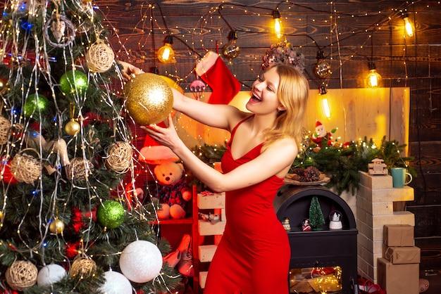 La ragazza festeggia il capodanno a casa vicino all'albero di natale. il vestito rosso dalla ragazza sexy celebra il buon natale. concetto di celebrazione di natale. festa aziendale. stagione dell'anno preferita. felicità e gioia