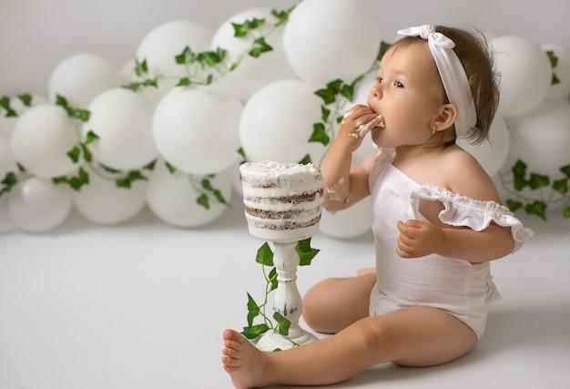 Una ragazza festeggia il suo primo compleanno e mangia una torta di compleanno