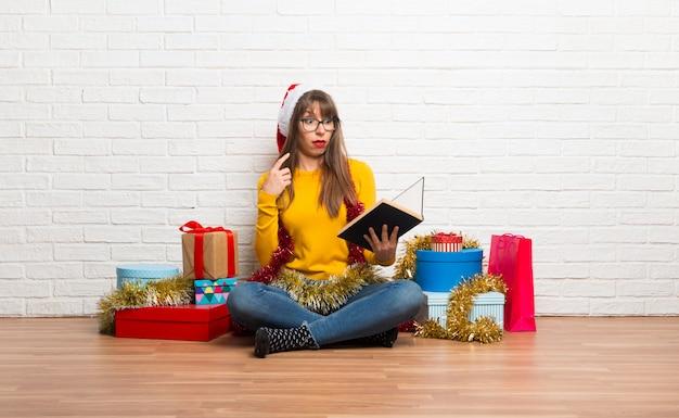 Ragazza che celebra le feste di natale che tiene un libro e sorpreso mentre gode della lettura