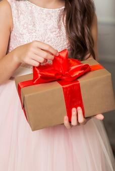 Una ragazza in un abito chic sta con un regalo di capodanno tra le mani sullo sfondo