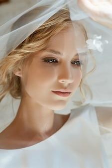 Ragazza in un vestito lungo elegante che si siede sul pavimento. abito da sposa bianco sul corpo della sposa