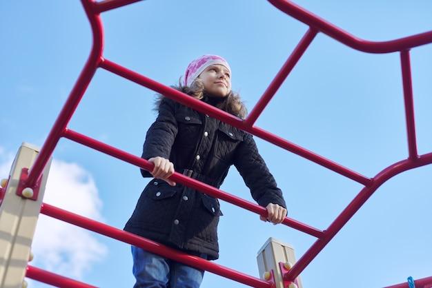 Bambina di 8, 9 anni su attrezzature sportive all'aperto