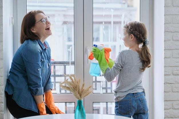 Bambina che aiuta la donna a lavare le finestre, fare le pulizie a casa