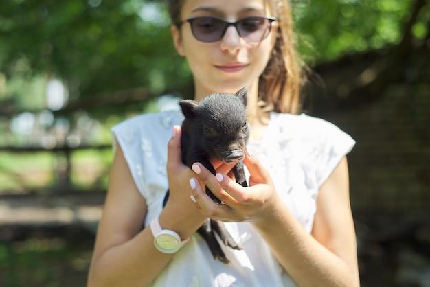 Bambina che tiene nelle mani del maialino neonato nero. fattoria, agricoltura, campagna, animali domestici, concetto di bambini