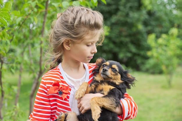 Bambina che abbraccia cane all'aperto, amicizia e amore tra piccolo proprietario e animale domestico.