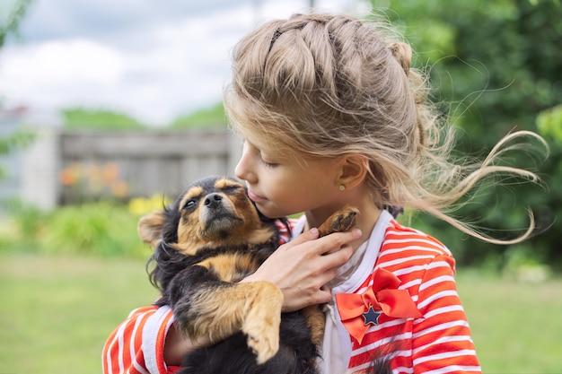 Bambina che abbraccia cane all'aperto, amicizia e amore tra piccolo proprietario e animale domestico