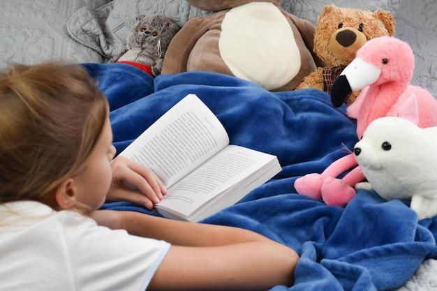Bambina si trova sul letto con un libro e giocattoli
