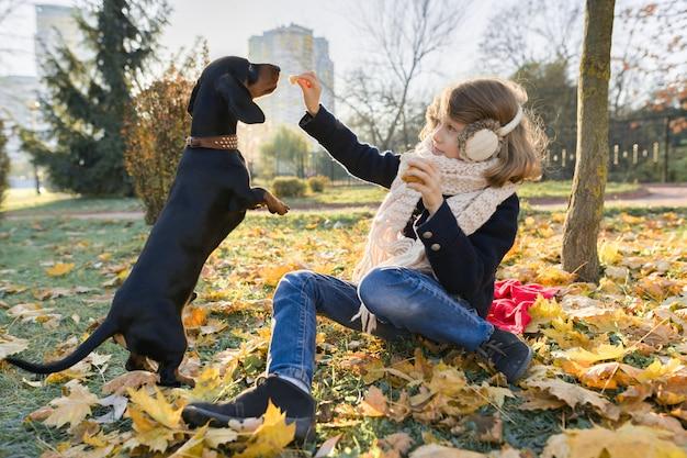 Bambino della ragazza che gioca con il cane del bassotto tedesco nel parco soleggiato di autunno