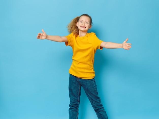 Bambina che posa in ritratto dello studio, superficie colorata